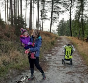 Child laughing in arms of her auntie on woodland trail with pushchair in background